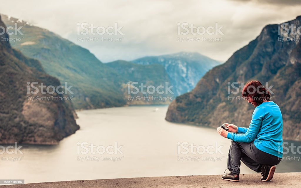 Female tourist taking photo at norwegian fjord royalty-free stock photo