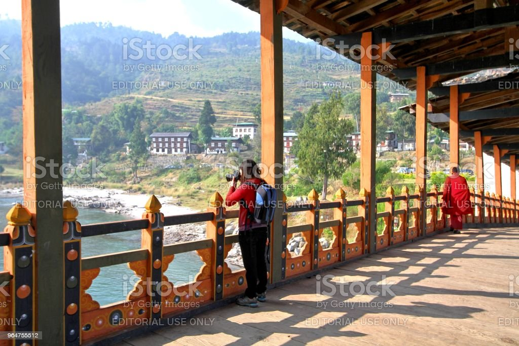 Female tourist taking photograph at PUNA MOCCHU BAZAM : Antique  wooden bridge at Punakha Dzong Monastery or Pungthang Dewachen Phodrang  Bhutan royalty-free stock photo