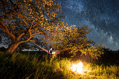 Female tourist using her laptop in the camping at night. Woman sitting in the hammock near campfire under trees and night sky with the moon