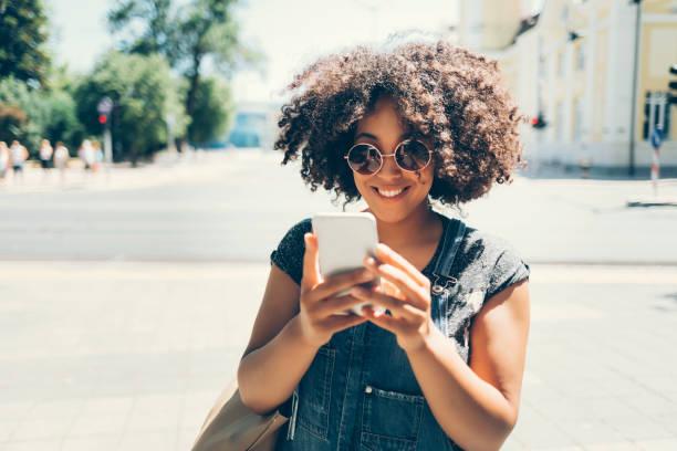 weibliche touristen auf der straße spazieren und mit smartphone - outdoor handy stock-fotos und bilder