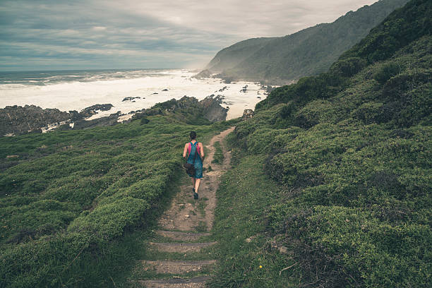 Female tourist walking on trail along wild coast. stock photo