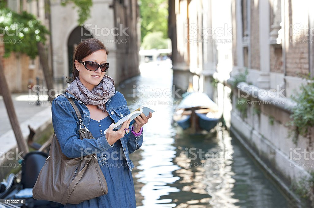 Female tourist with guide book in historic town, Italy stock photo