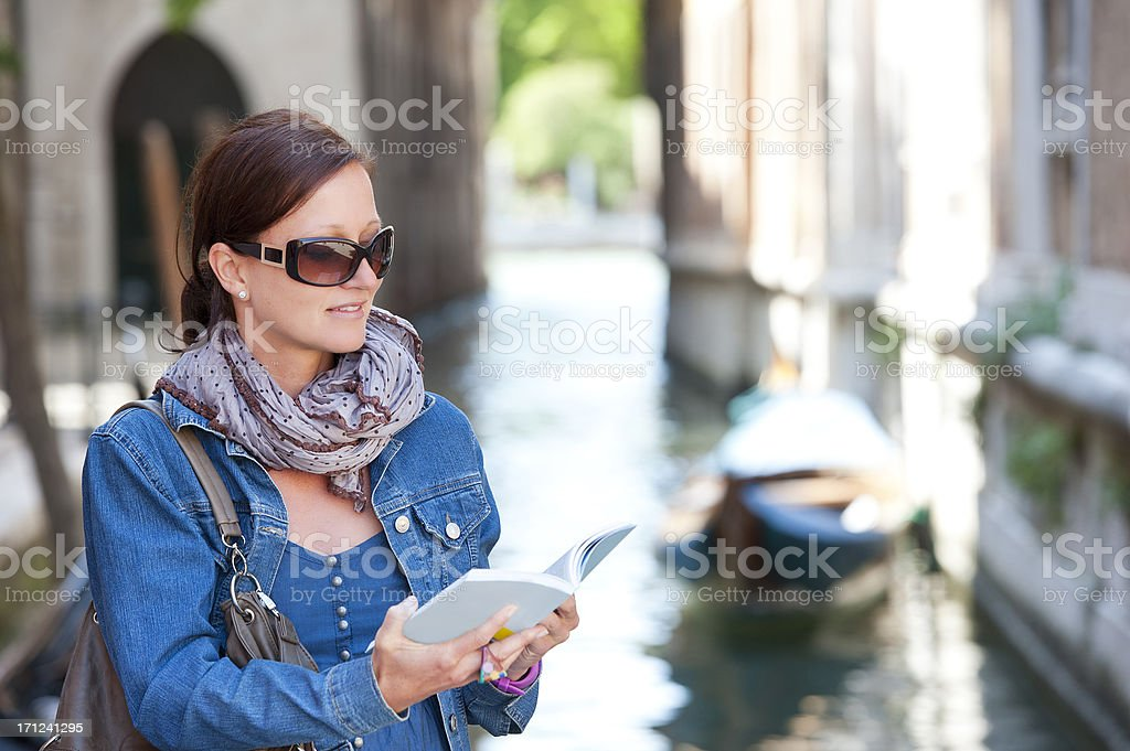 Female tourist with guide book in historic town, Italy royalty-free stock photo