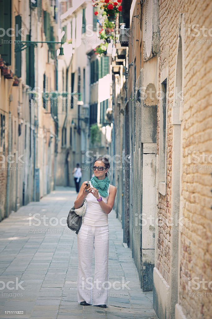 Female tourist with smart phone in historic town, Italy royalty-free stock photo