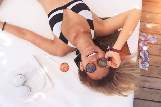 vrouwelijke toerist met zonnebril liggen en lachend door de zee - gebruind stockfoto's en -beelden