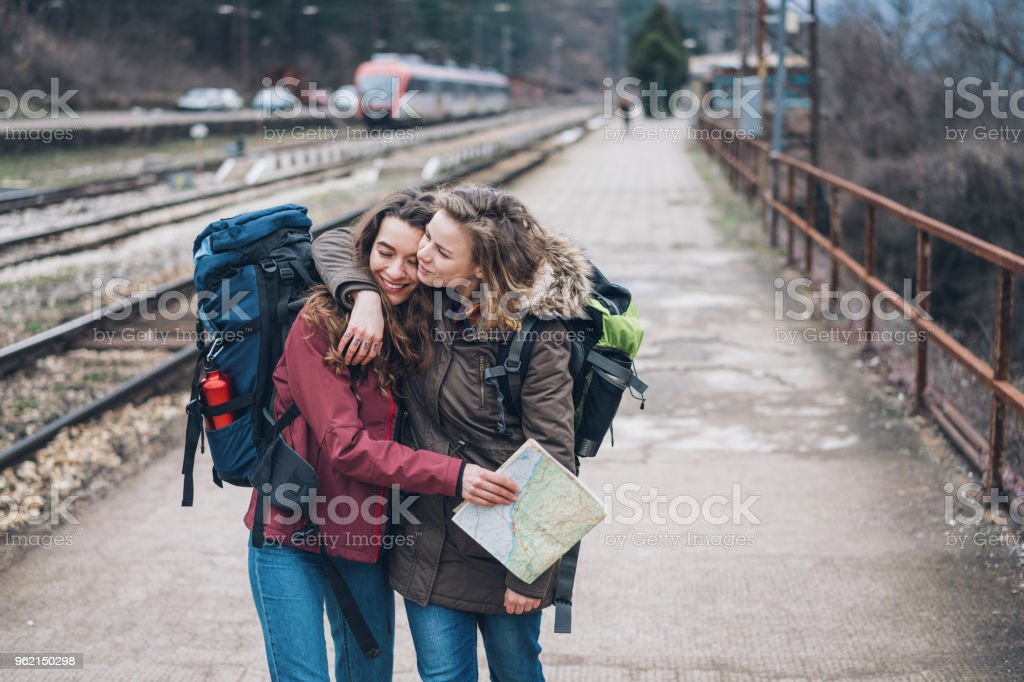 Female tourists cuddling while walking along the railway tracks Стоковые фото Стоковая фотография