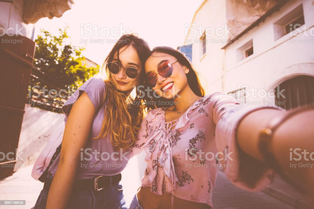 Female tourists taking a selfie in Italian old city streets stock photo