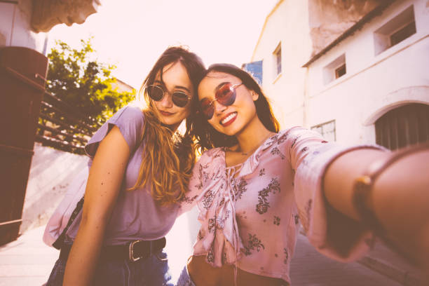 female tourists taking a selfie in italian old city streets - pics for cool girl stock pictures, royalty-free photos & images