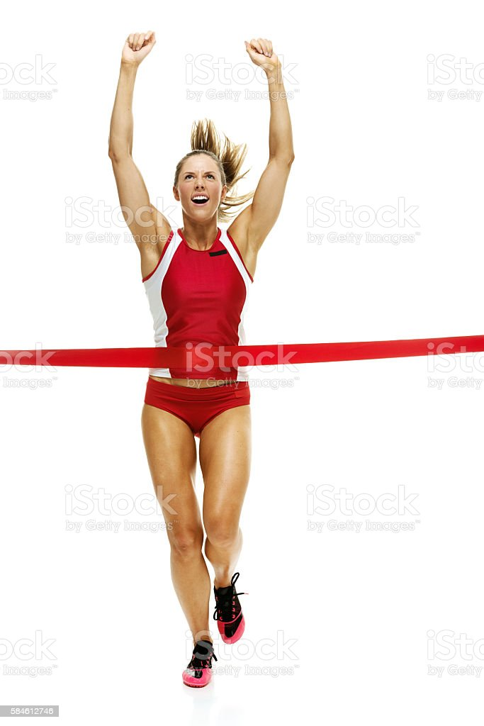 Female track and field runner crosses finishing line stock photo