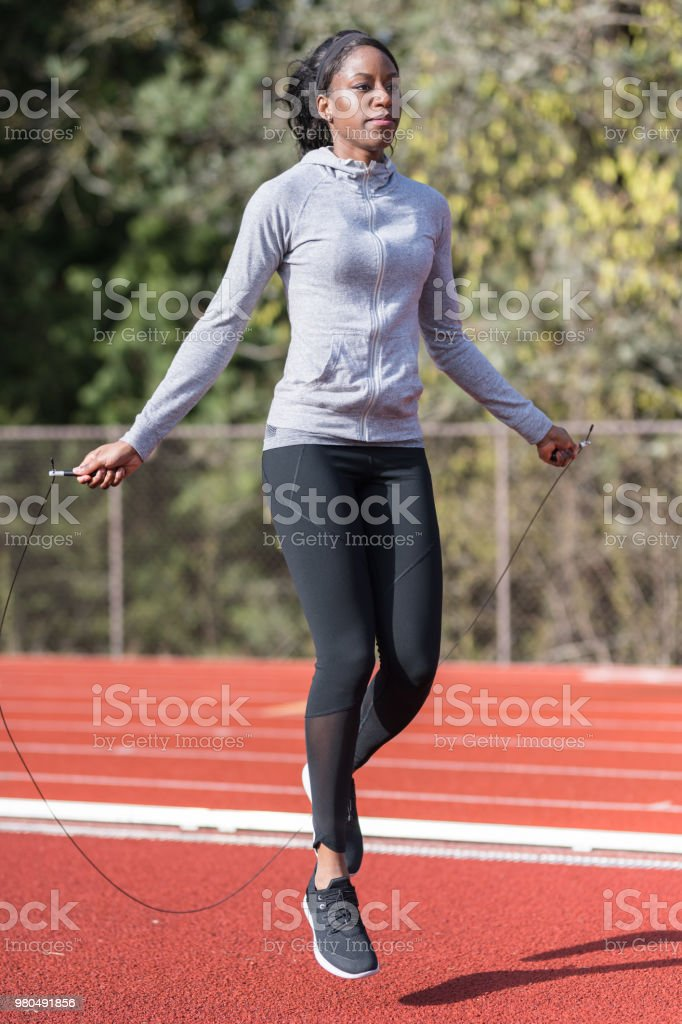 Female track athlete does warmups with a jump rope stock photo