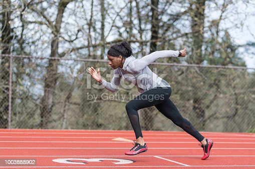 An African American female track athlete trains at a stadium. She is running sprints on the field. The shot is of her in profile as she runs from right to left.