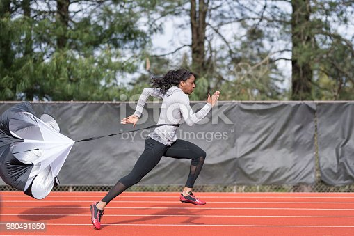 An African American athlete runs sprint drills on a stadium track. She is running with a parachute attached to her for resistance training.
