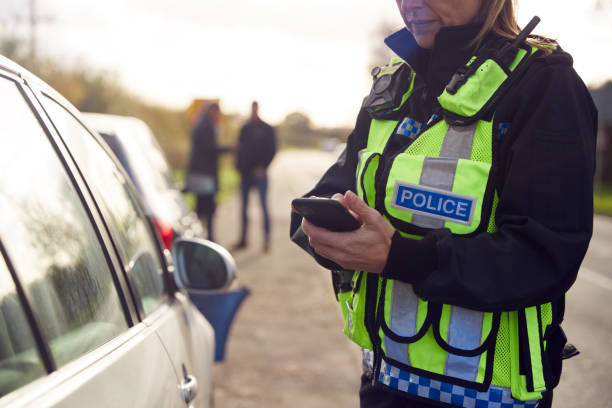 Female Traffic Police Officer Recording Details Of Road Traffic Accident On Mobile Phone stock photo