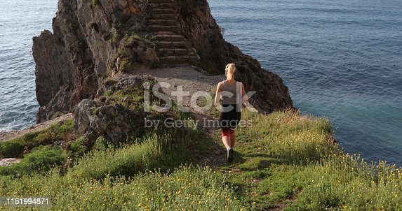 She looks off to staircase in cliff over sea ahead
