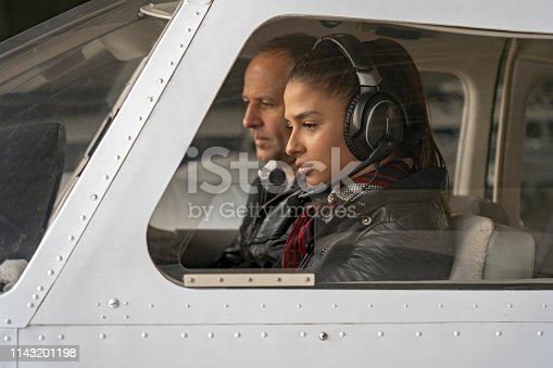 Portrait of attractive young woman trainee pilot with headset preparing to fly. She is sitting next to istructor and looking at dashboard of the private plane.