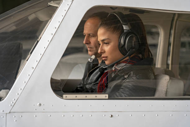 Female Trainee Pilot and Flight Instructor in an Aircraft Cockpit Portrait of attractive young woman trainee pilot with headset preparing to fly. She is sitting next to istructor and looking at dashboard of the private plane. pilot stock pictures, royalty-free photos & images