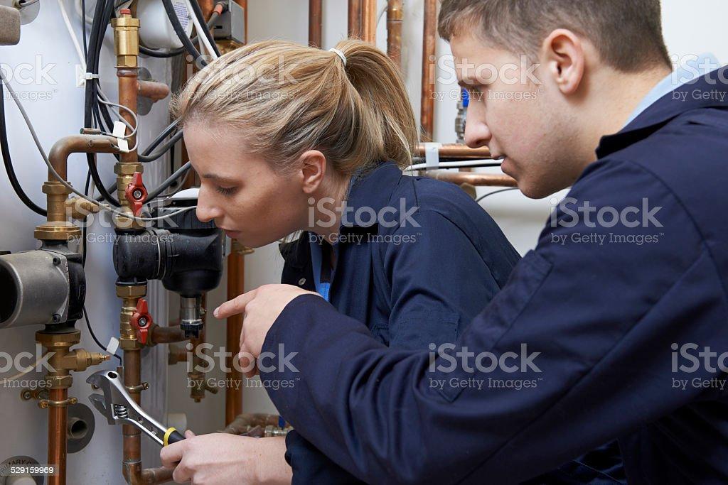 Weibliche Trainee Klempner Arbeiten an der Zentralheizung Boiler - Lizenzfrei Arbeiten Stock-Foto