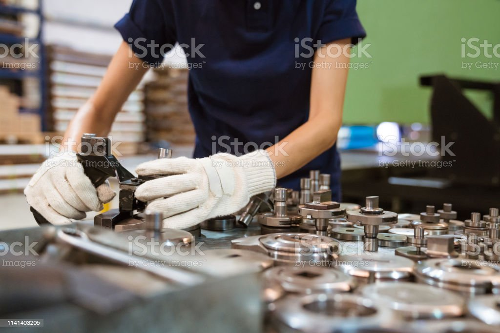 Female trainee using manufacturing machinery Midsection of female apprentice using manufacturing machinery. Engineer is working in factory. She is in blue t-shirt. 30-34 Years Stock Photo