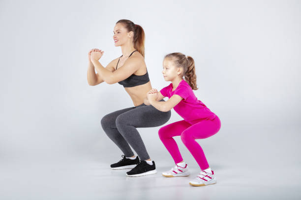 Female trainer and 10 years old girl are doing gym exercises stock photo