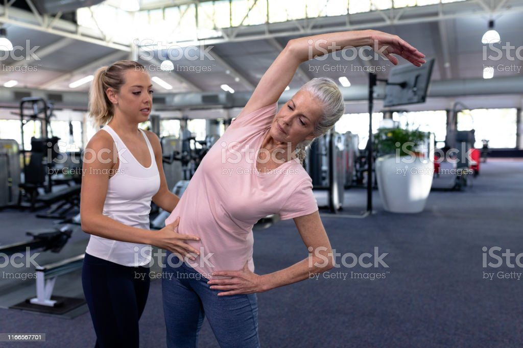 Front view of female trainer assisting active senior woman in modern...