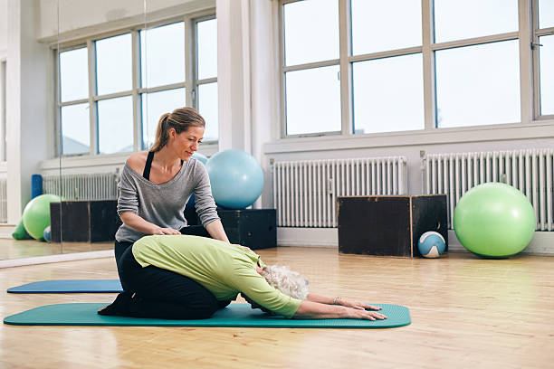 Female trainer helping senior woman doing yoga Female trainer helping senior woman doing yoga. Elder woman bending over a exercise mat with personal instructor helping at gym. childs pose stock pictures, royalty-free photos & images