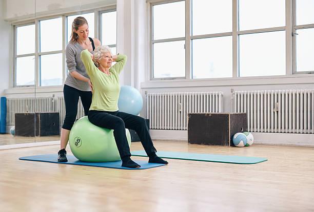 femmina trainer aiutando senior donna esercizio in palestra - metodo pilates foto e immagini stock