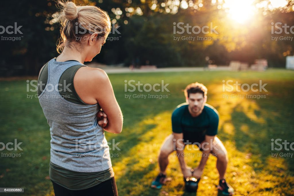 Female trainer in the park with man working out stock photo