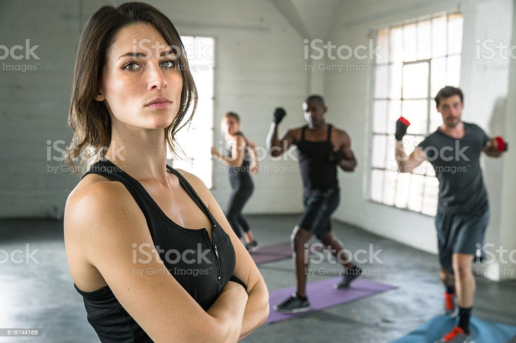 Female trainer instructor gym arms crossed fighter leader training class stock photo