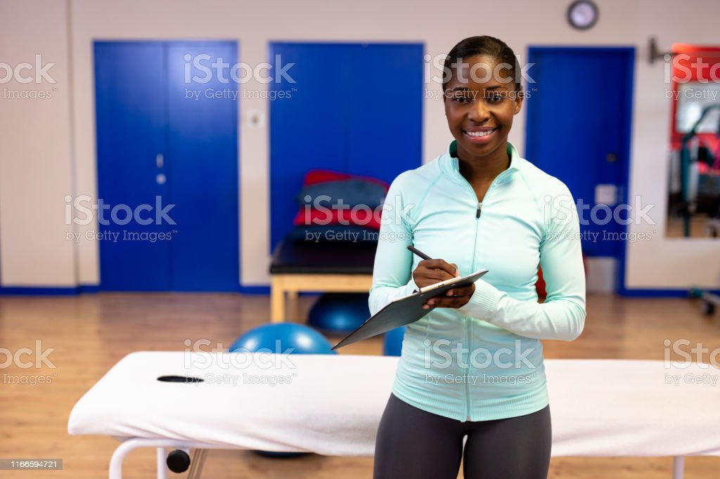 Happy female trainer looking at camera while writing on clipboard in...