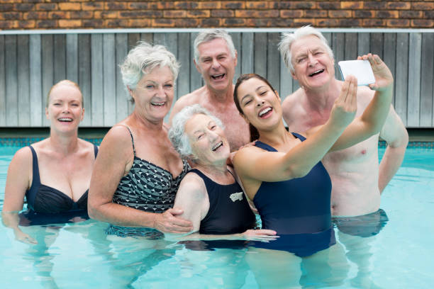 Female trainer taking selfie with senior swimmers in pool stock photo