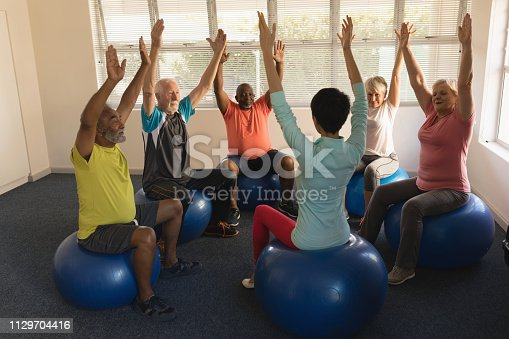 istock Female trainer training senior people in performing exercise 1129704416