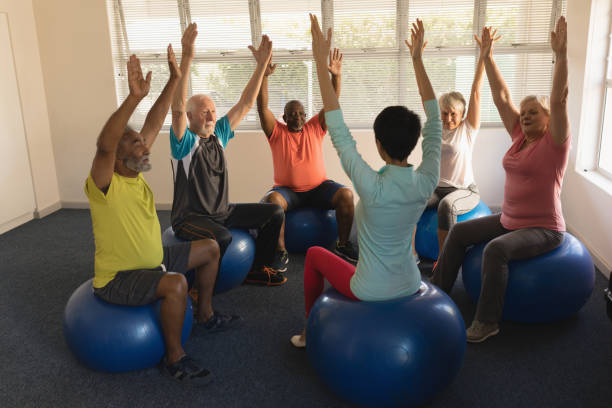 Female trainer training senior people in performing exercise Front view of female trainer training senior people in performing exercise ball at home recreational pursuit stock pictures, royalty-free photos & images