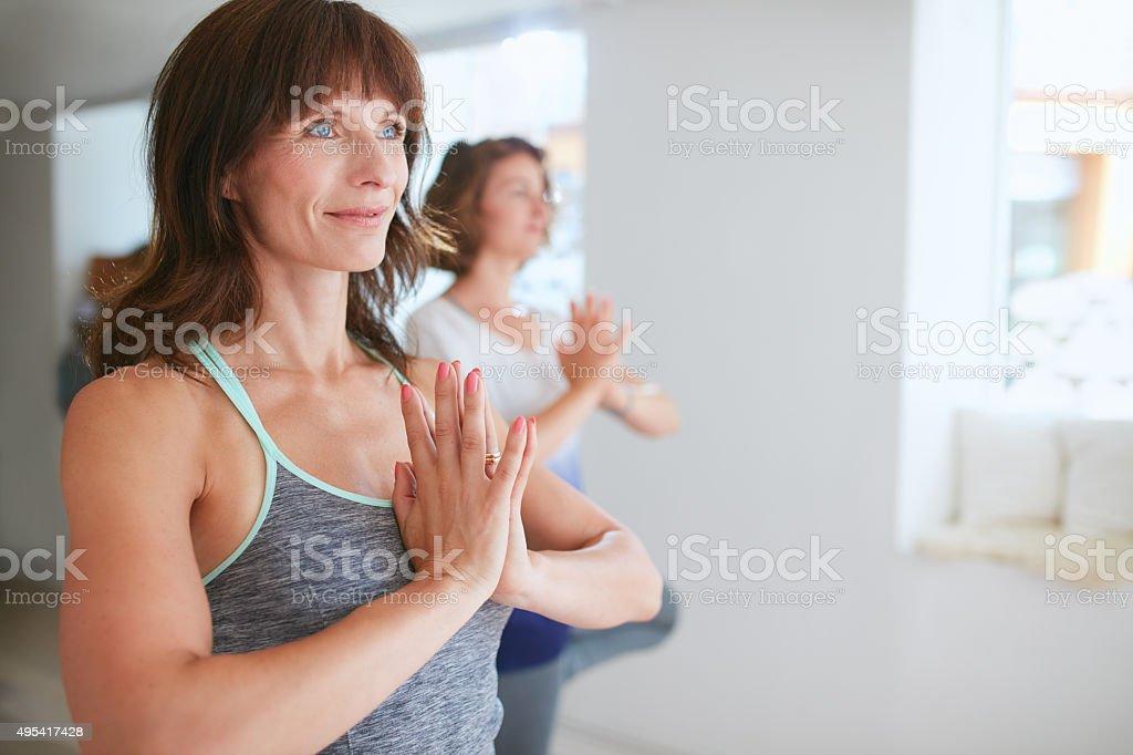 Female trainer with student doing Vrikshasana stock photo