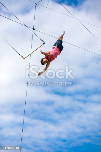 Female trapeze artist flying in the blue sky