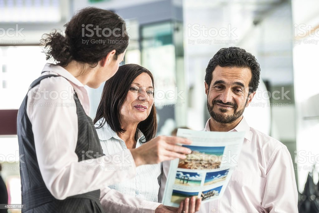 Female Travel Agent With Customers stock photo