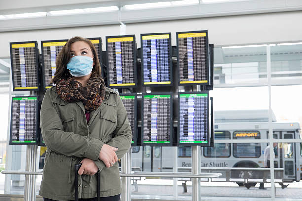 Female Traveler Fearful of Ebola Wears a Mask at Airport stock photo