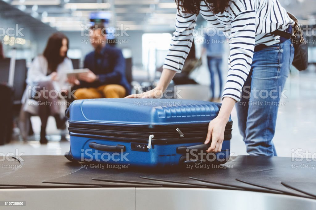 Female traveler picking up suitcase from baggage claim line stock photo