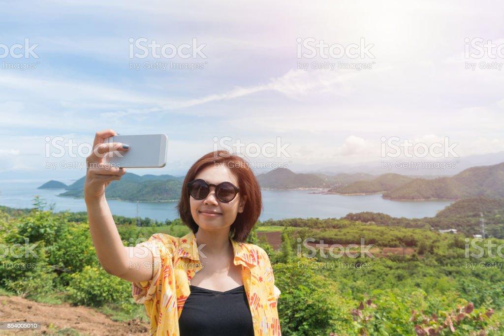 Female traveler selfie with her smart phone and beautiful landscape at kanchanaburi thailand stock photo