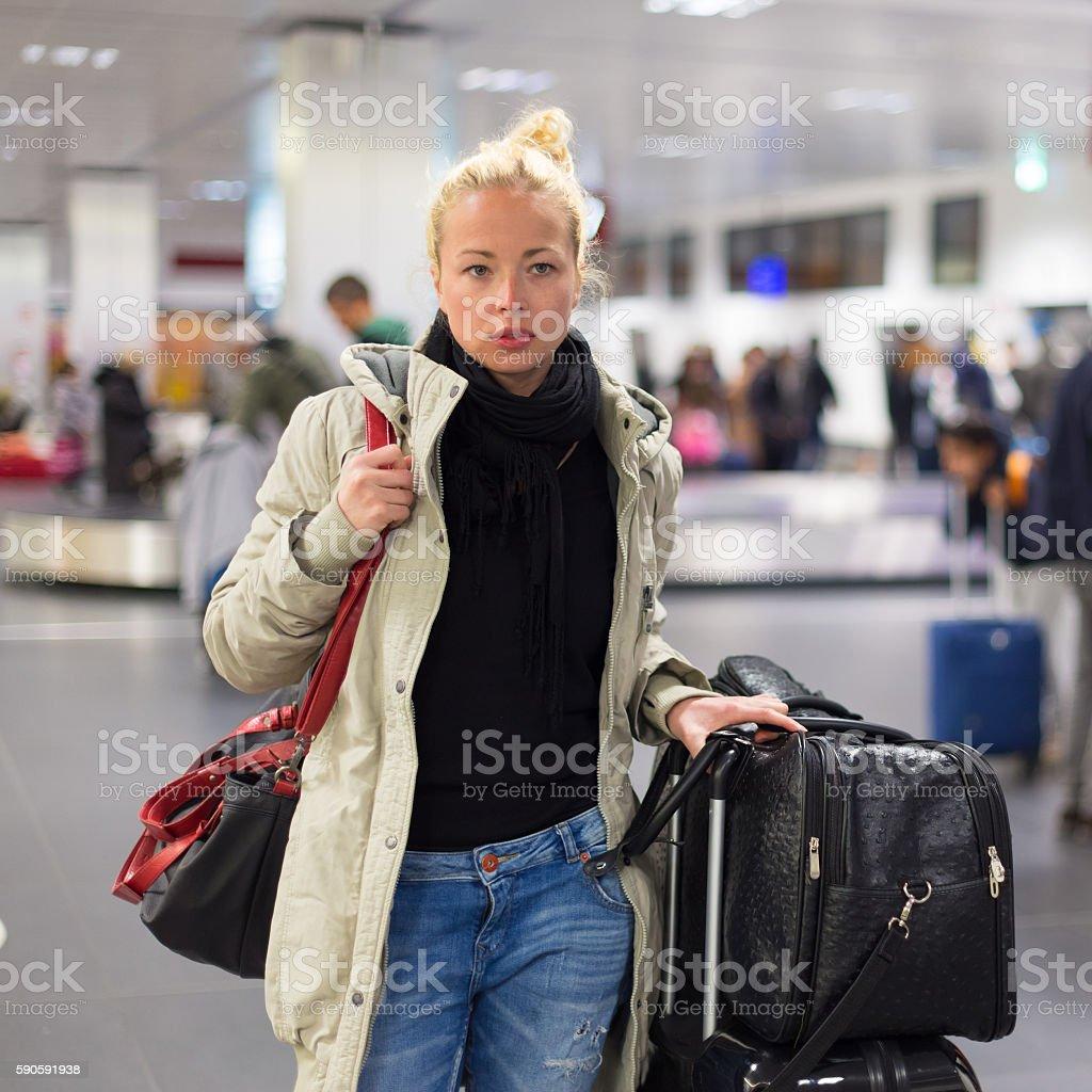Weibliche Reisende die Beförderung von Gepäck im Flughafen. – Foto