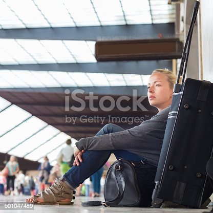 Tired female traveler waiting for departure, sitting on the station floor with all her luggage.