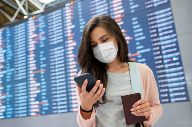 Female traveler wearing a facemask at the airport while texting on her phone stock photo