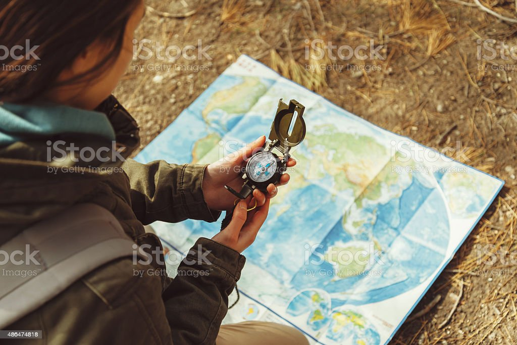 Female traveler with a compass and map stock photo