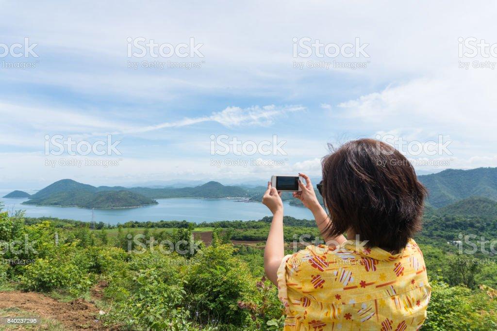 Female traveler with smart phone taking a photo of beautiful landscape at kanchanaburi thailand stock photo