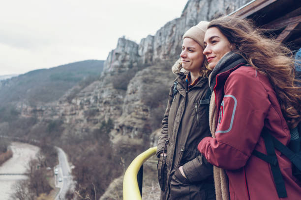 Female travelers standing on high terrace in the rocks and looking at the canyon stock photo