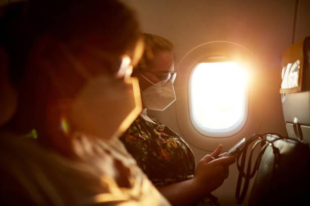 Female Travelers Wearing KN95 Masks on Airplane stock photo