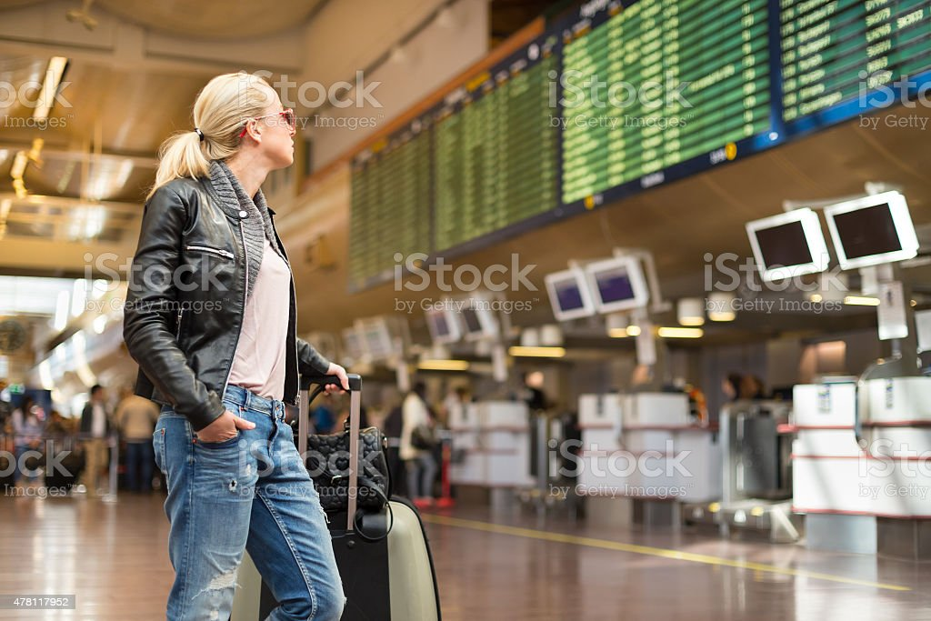 Female traveller checking flight departures board. stock photo