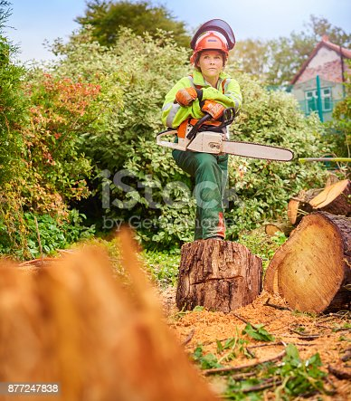 a young female chainsaw operative stands proudly next to her fallen tree