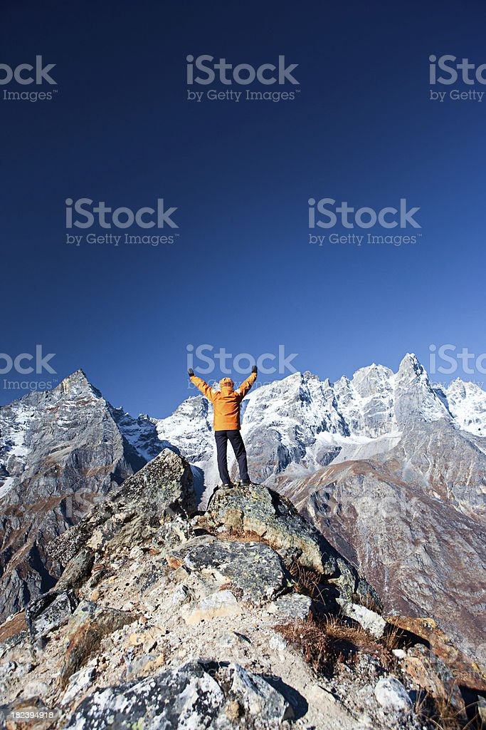 Female trekker lifts her arms in victory, Himalaya Range royalty-free stock photo