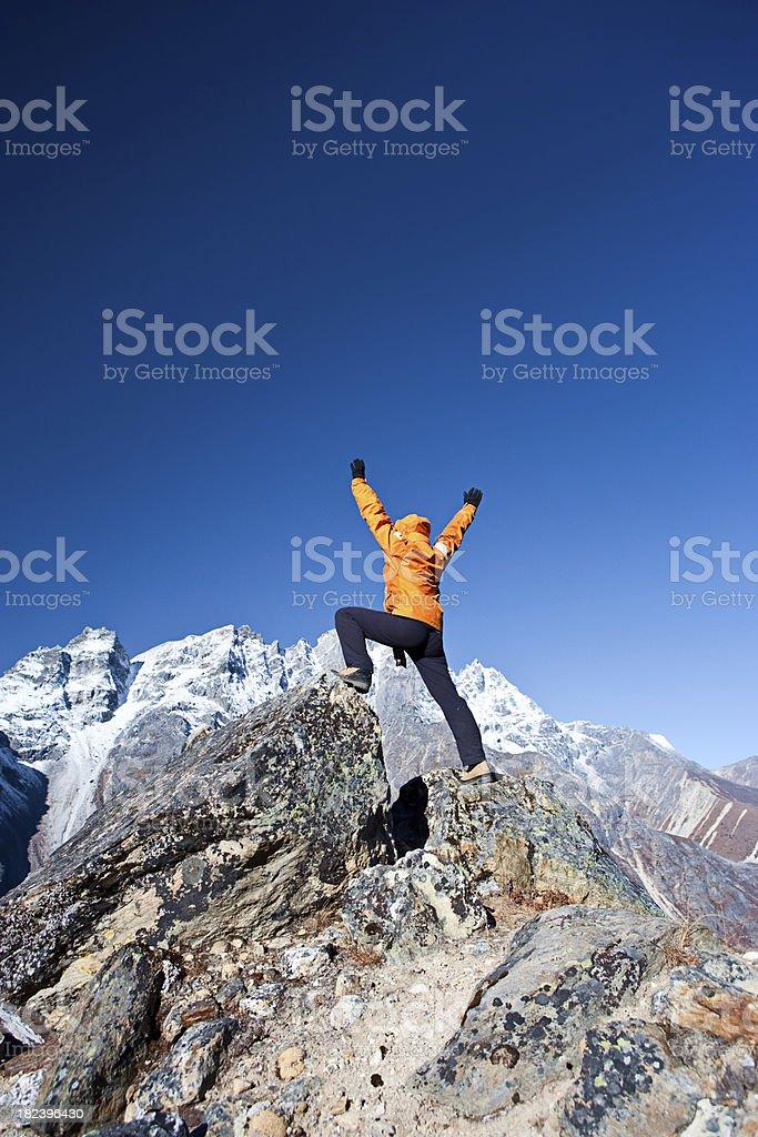 Female trekker lifts her arms in victory, Himalaya Range stock photo