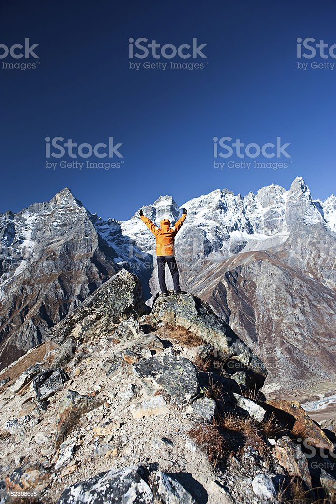 Female trekker lifts her arms in victory, Himalayas stock photo